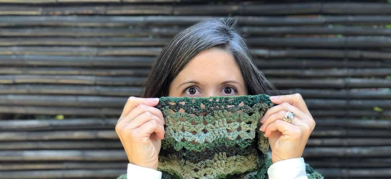 Woman peeking over green cowl.