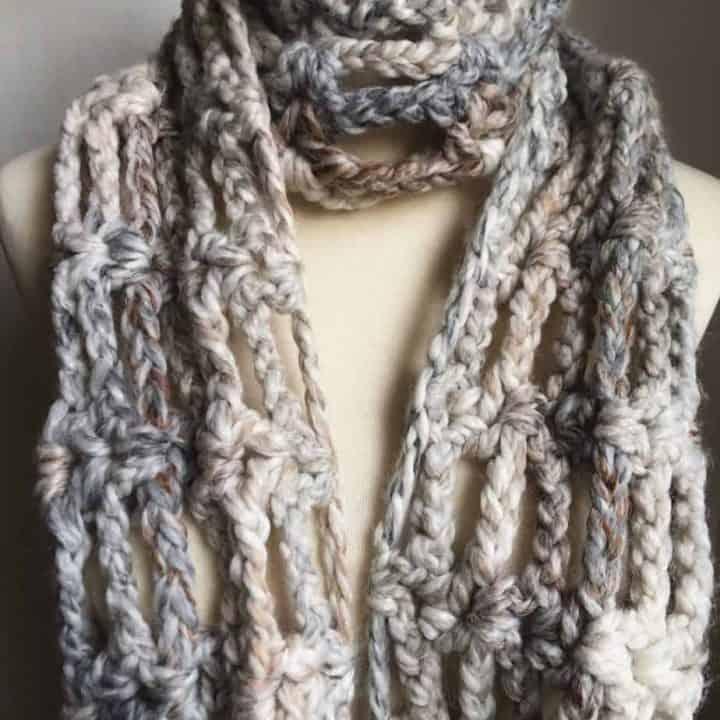 Bulky yarn scarf in grey on mannequin.