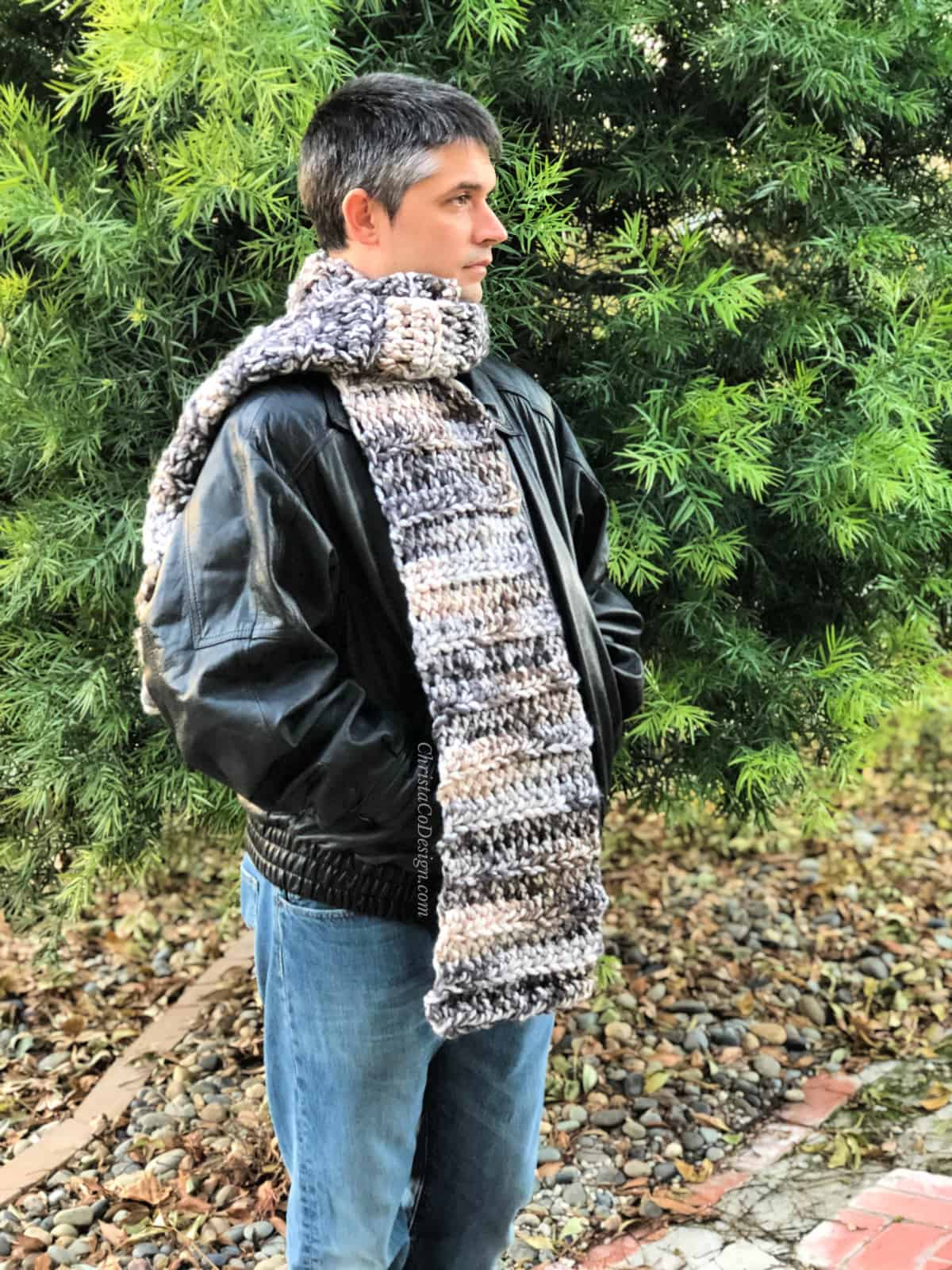 Man in black leather jacket in front of tree wrapped crochet super scarf.