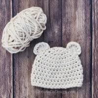Baby bear chunky crochet beanie flat in cream with yarn ball.