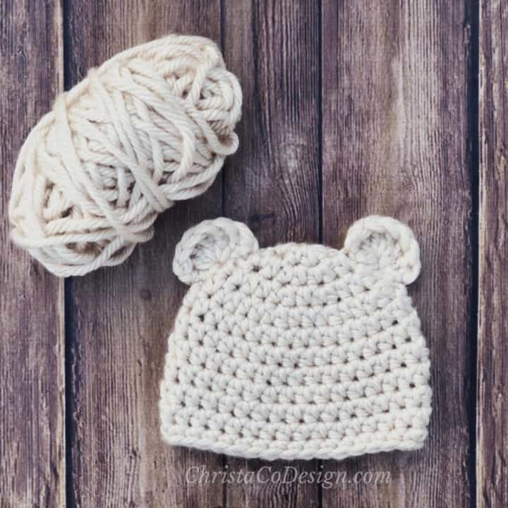 Baby bear chunky crochet beanie flat in cream with yarn ball.