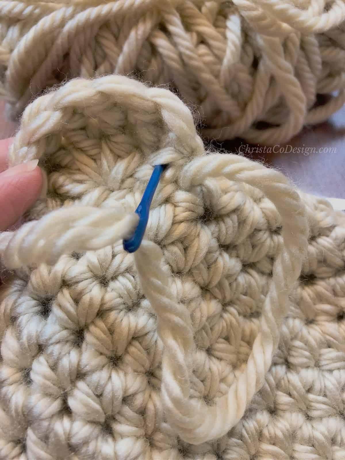 Seaming crochet bear ear to hat.