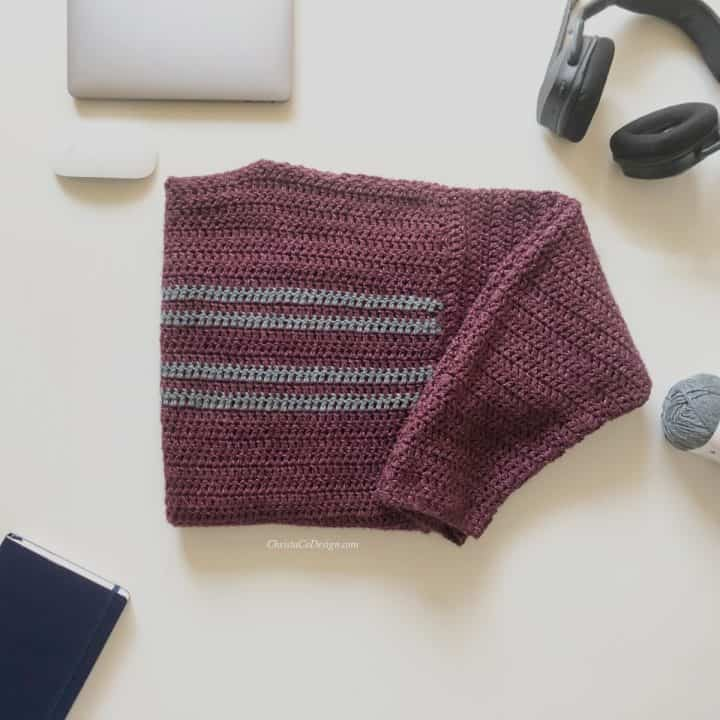 Mens simple striped crochet sweater in burgundy with grey stripes folded on table.