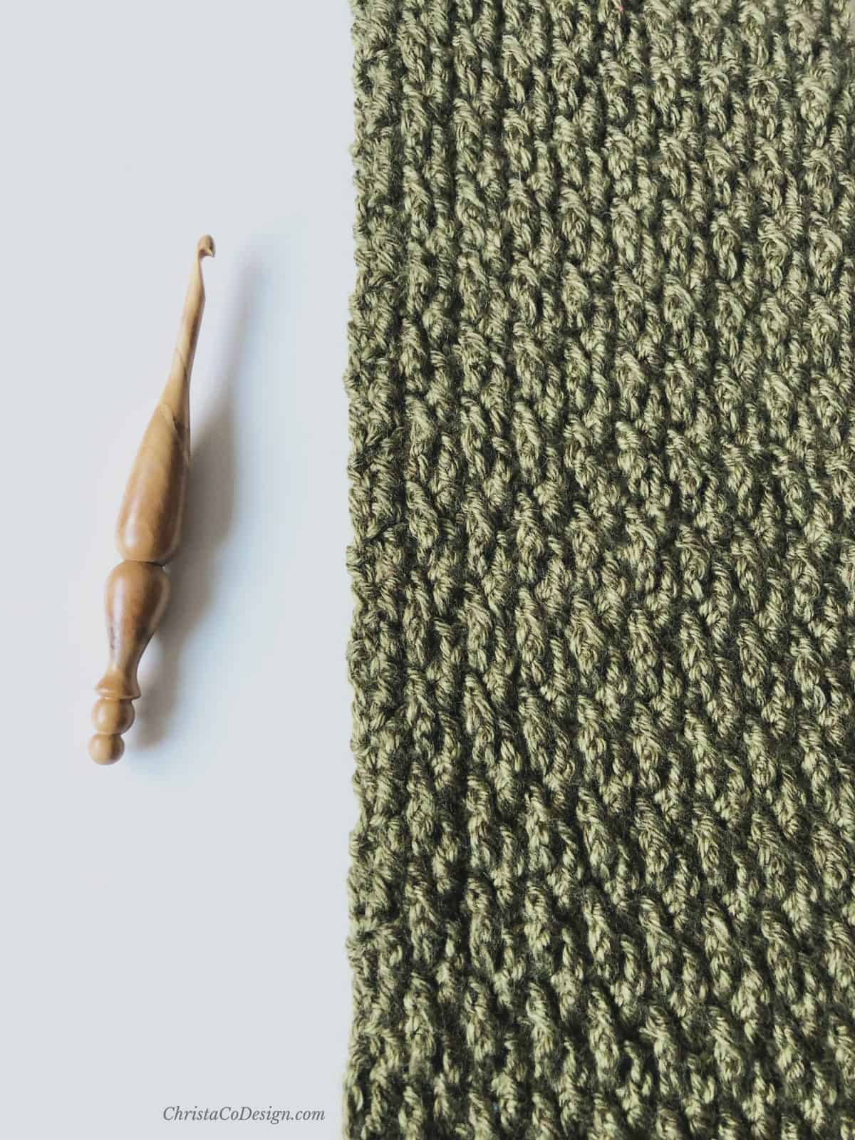 picture of wooden crochet hook and textured crochet scarf in green