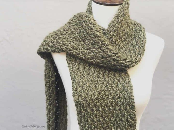 Green textured crochet scarf on mannequin.