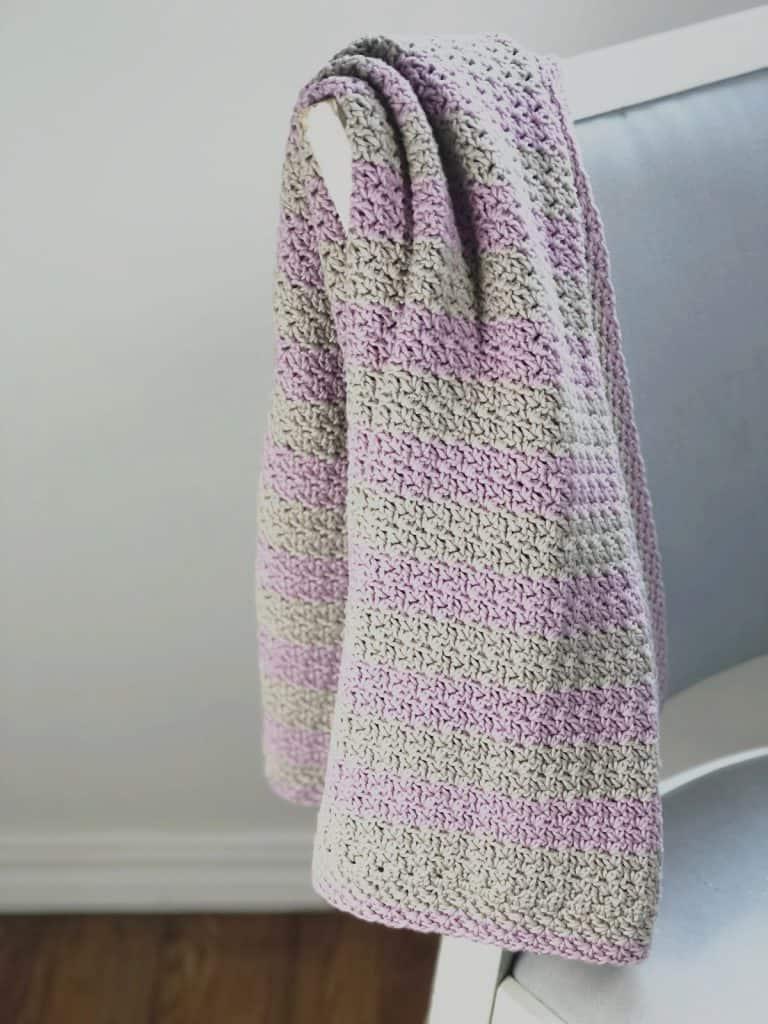 Pink stripe blanket draped on chair.