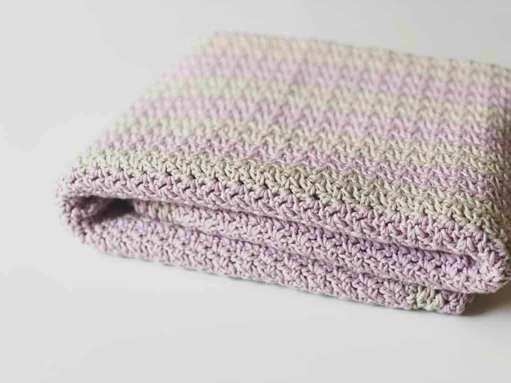 Folded pink and grey striped crochet blanket.