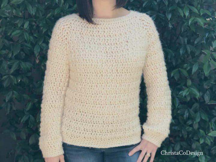 Woman in cream fuzzy crochet sweater.