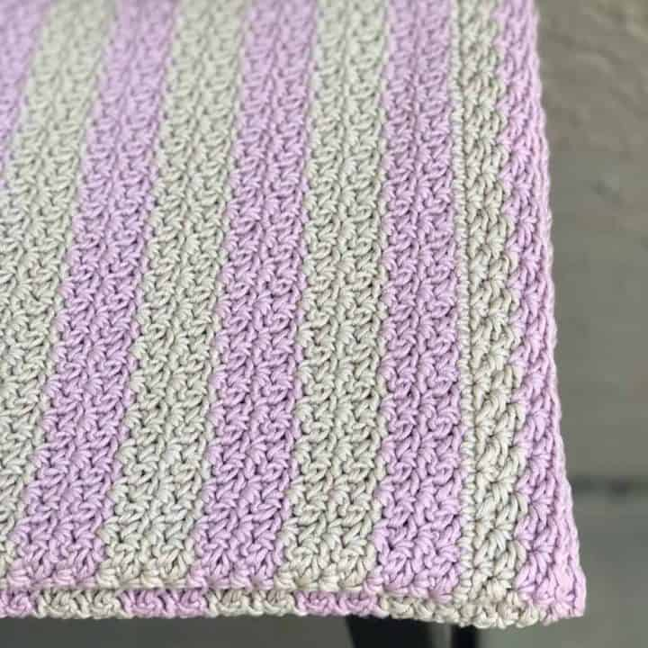Pink and grey striped blanket on stool.