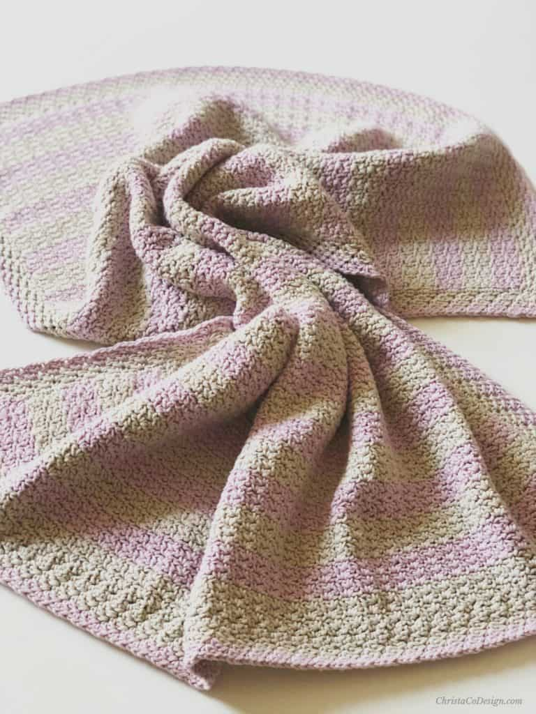 Twisted flat crochet striped blanket in pink and grey.