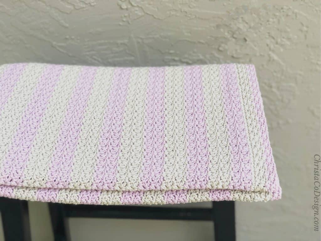 Folded striped blanket on stool.