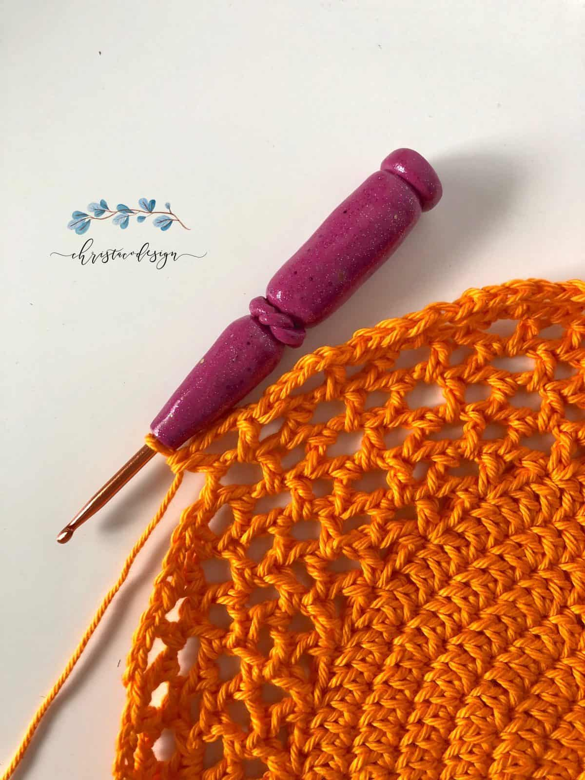 Free crochet tote bag pattern worked in the round with solid bottom progress with pink hook.