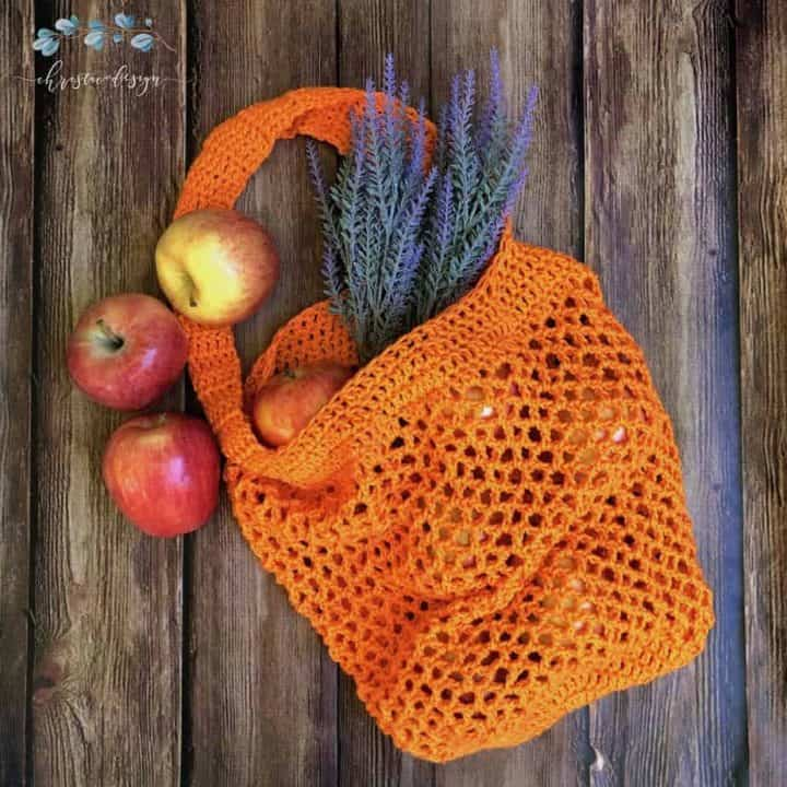 Free crochet market tote bag pattern in orange with apples and lavender on wood backdrop.