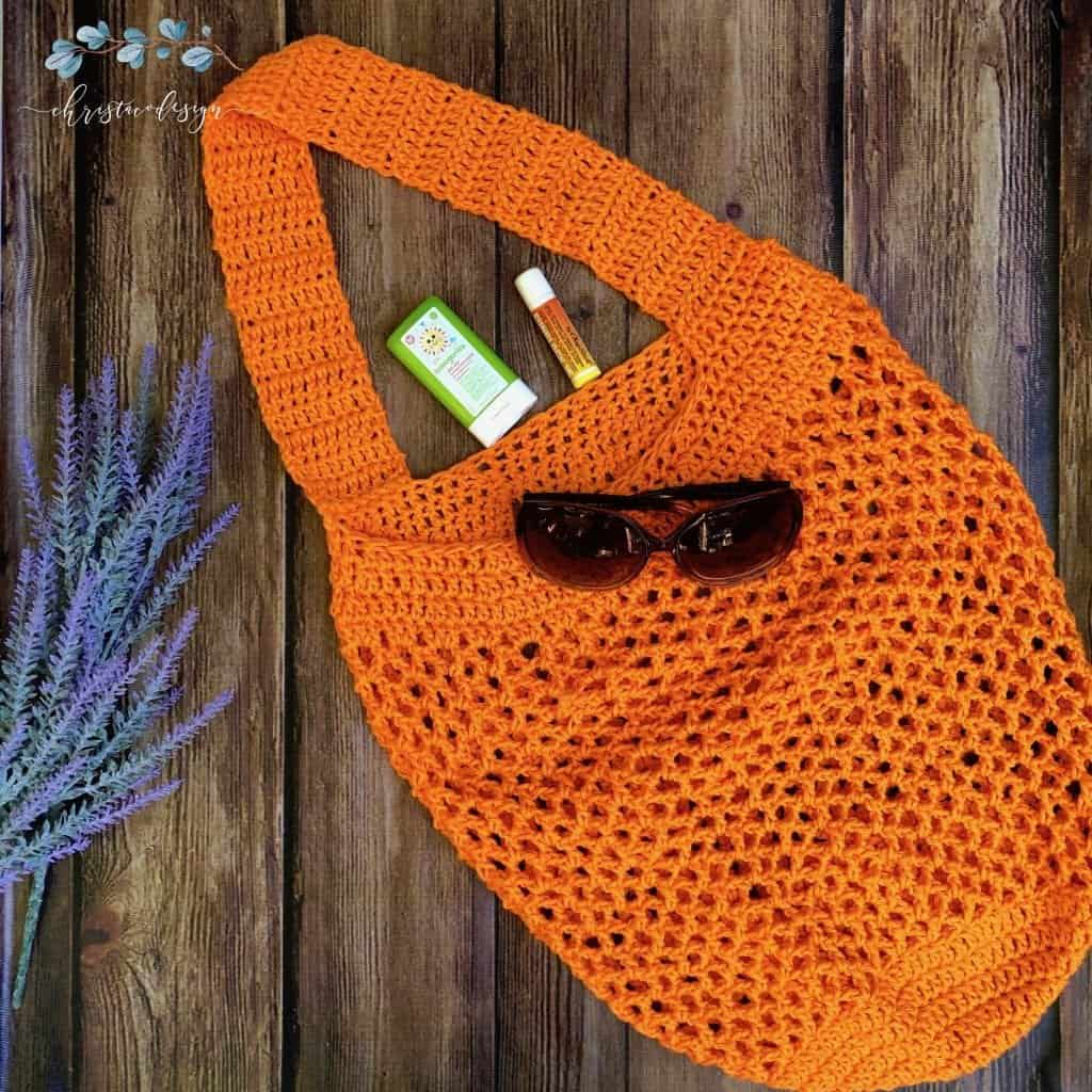 picture of orange beach bag with sunglasses flat