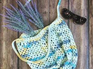 Free crochet tote bag pattern in blue and yellow crochet mesh flat with lavender.