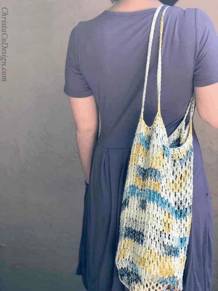 June tote free crochet tote bag slung over shoulder.