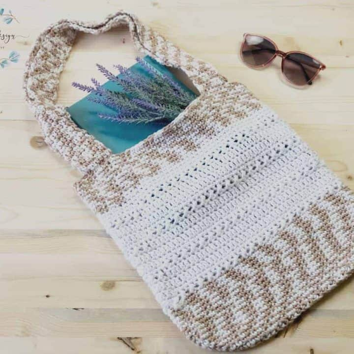 Free crochet tote bag pattern in white cotton yarn with notebook and lavender inside.