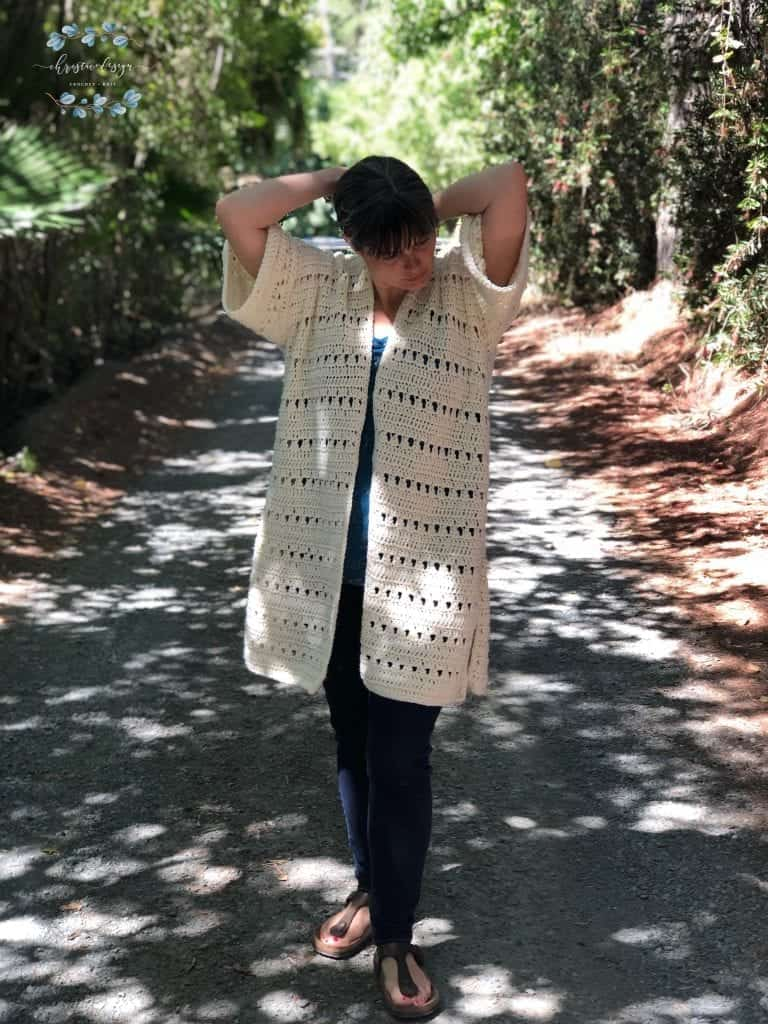 Picture of woman shaded wearing summer crochet cardigan cream colored