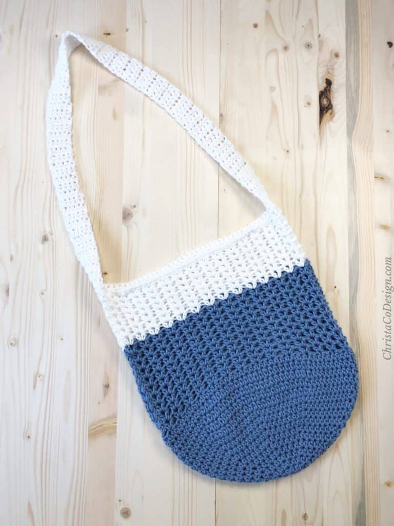 Blue and white crochet market tote bag free pattern on light wood back ground.