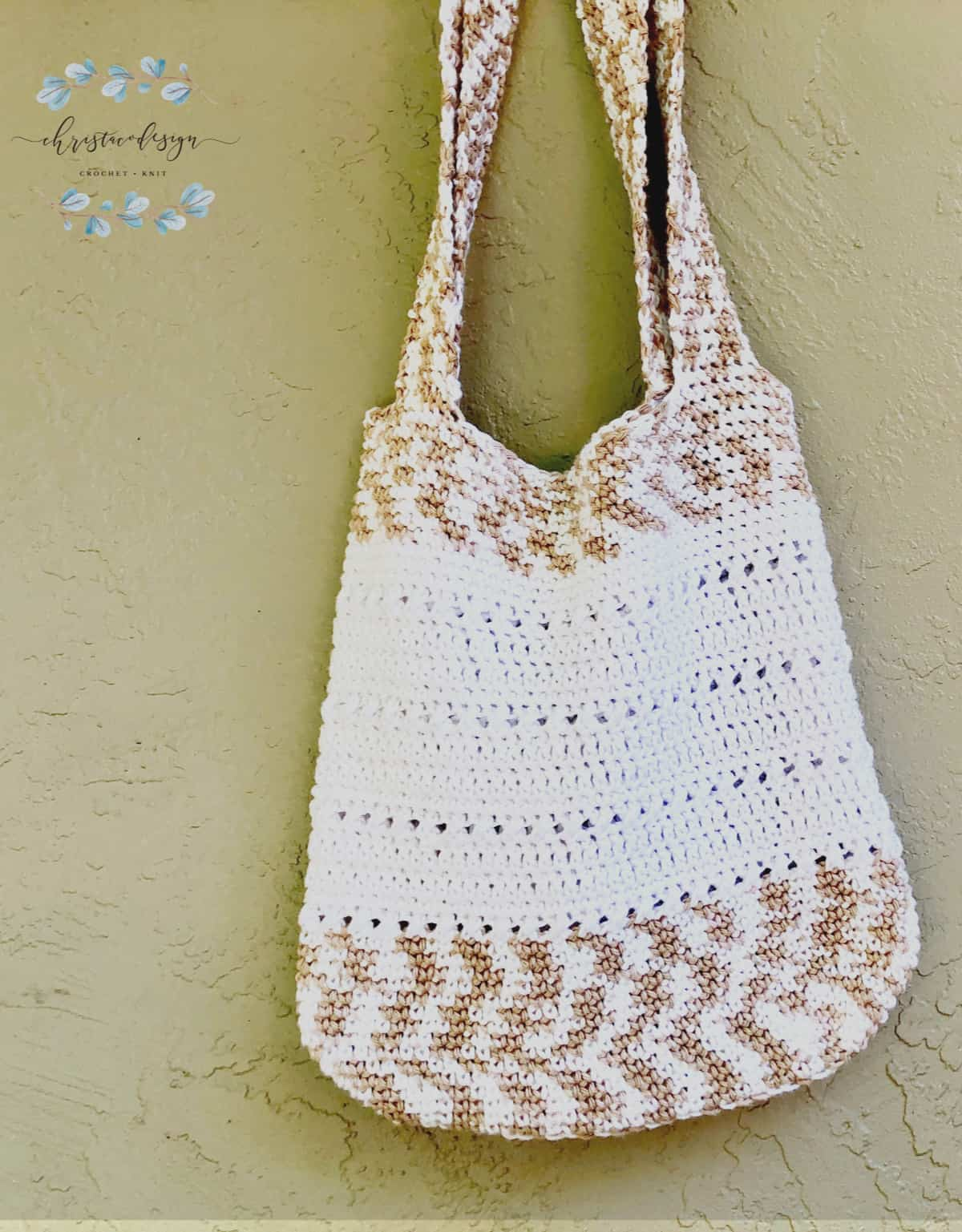 Free crochet tote bag pattern  in white and beige variegated cotton yarn hanging.