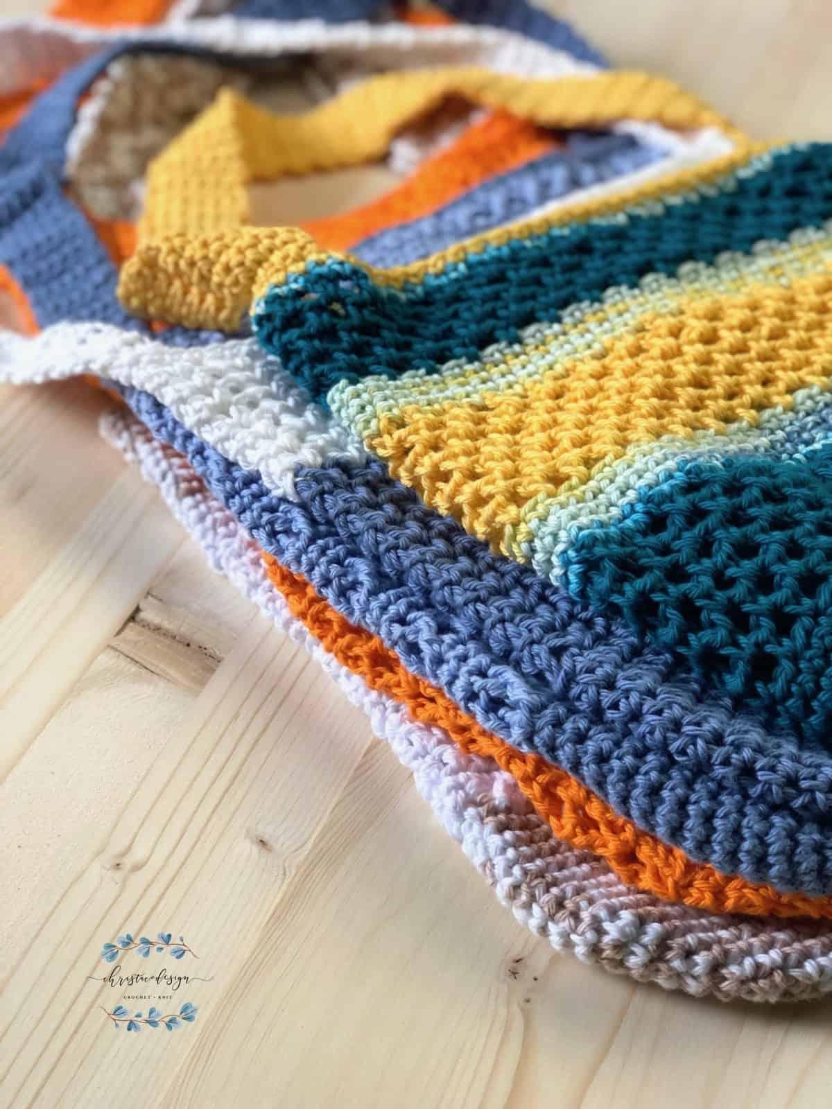 Coastal sun tote on stack of free crochet market bag patterns.