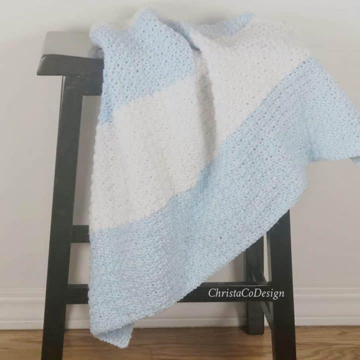 Crochet striped blue and white blanket on stool.