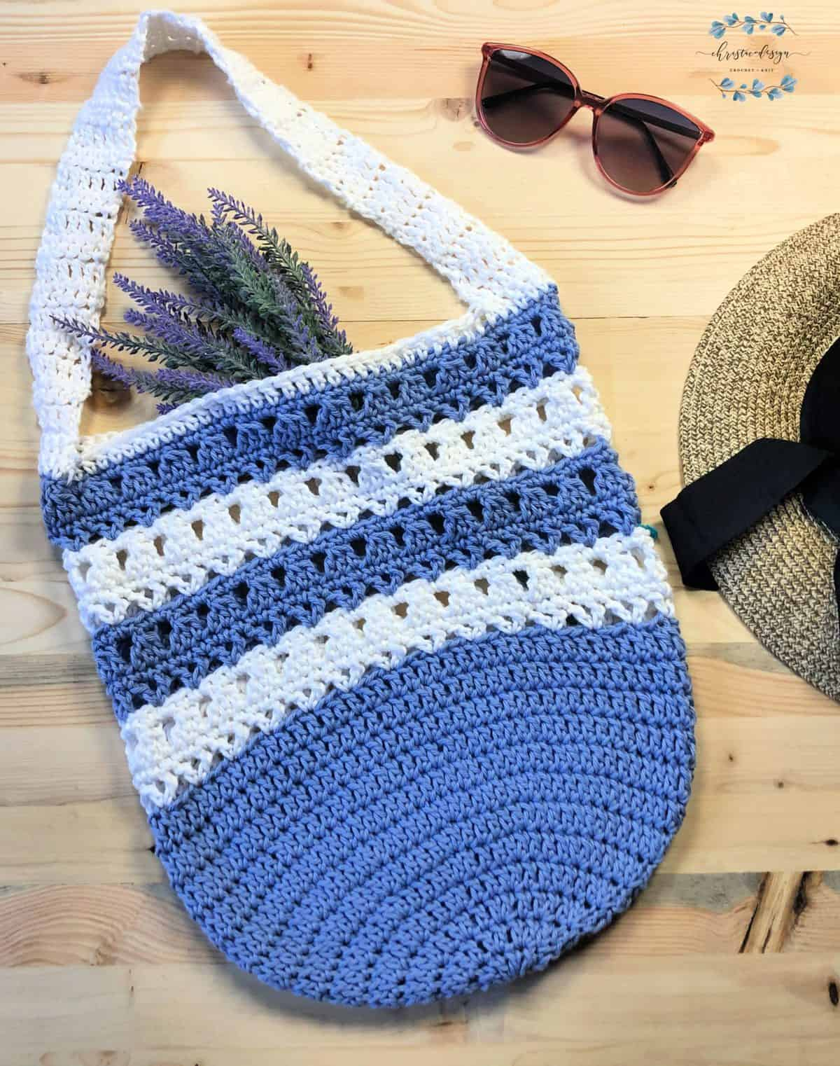 picture of violet striped free crochet market tote pattern flat with glasses and hat flat lay