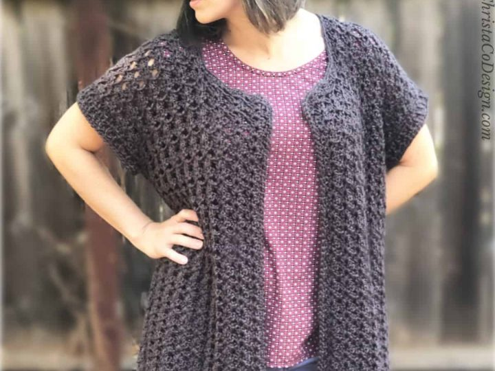 Woman outside in black crochet cardigan with short sleeves.