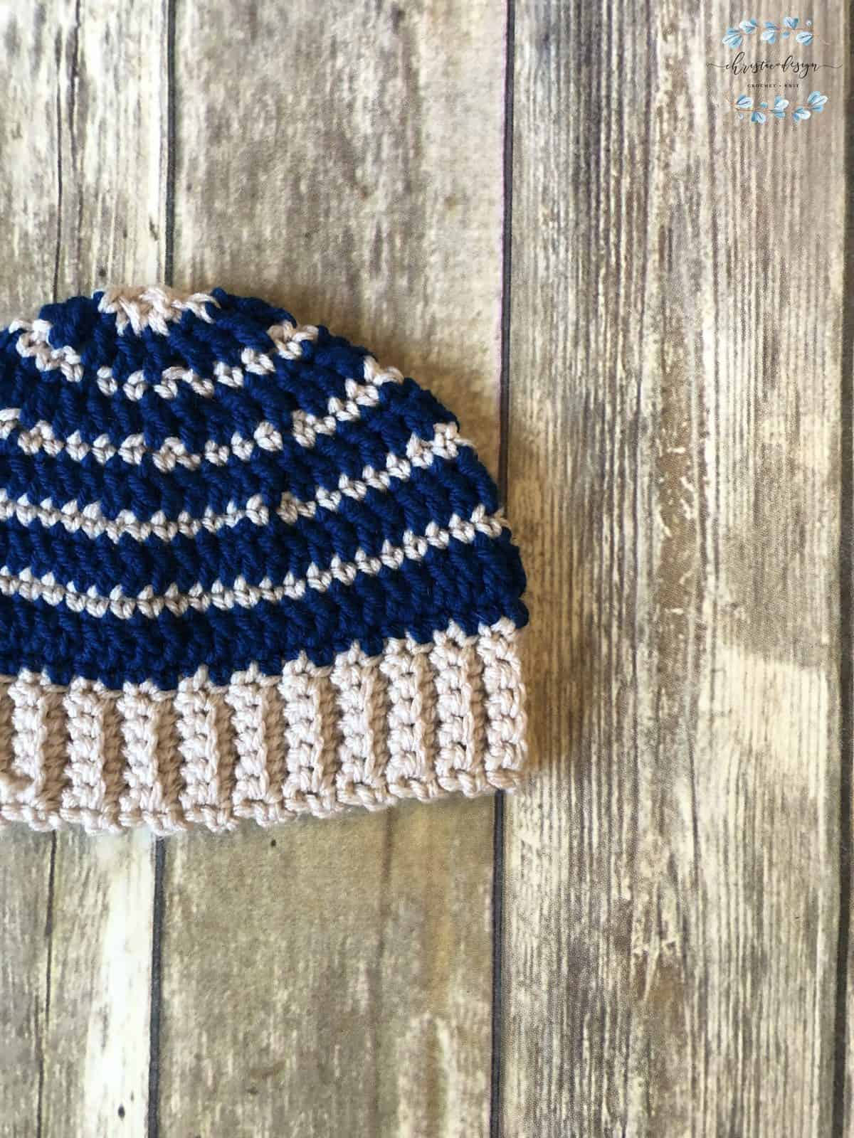 crochet bottom up hat with stripes of dark blue and stone grey