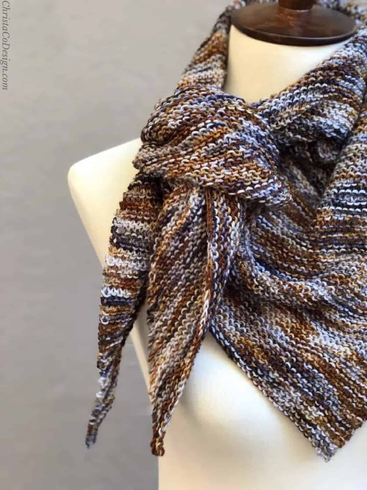 Knit triangle scarf tied loosely on side like neckerchief.