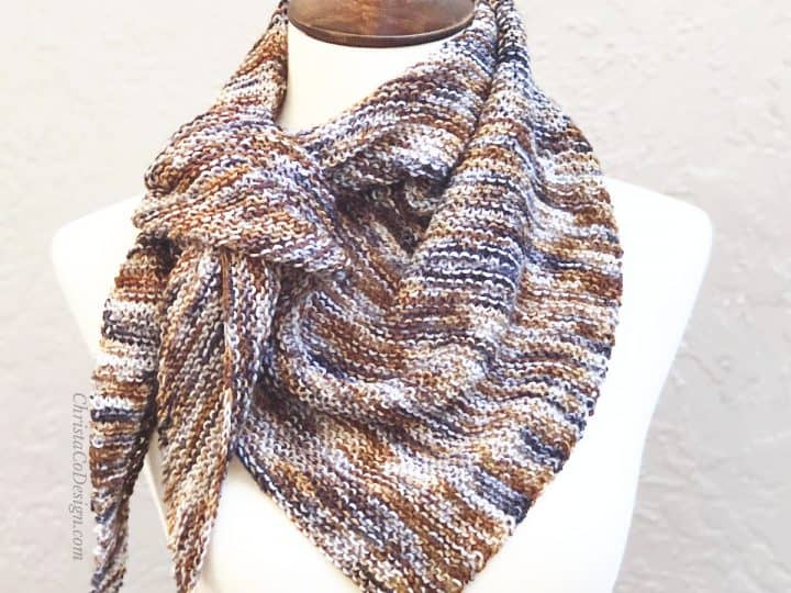 Triangle easy scarf knitting pattern for beginners in multi colored yarn of brown tied on mannequin.