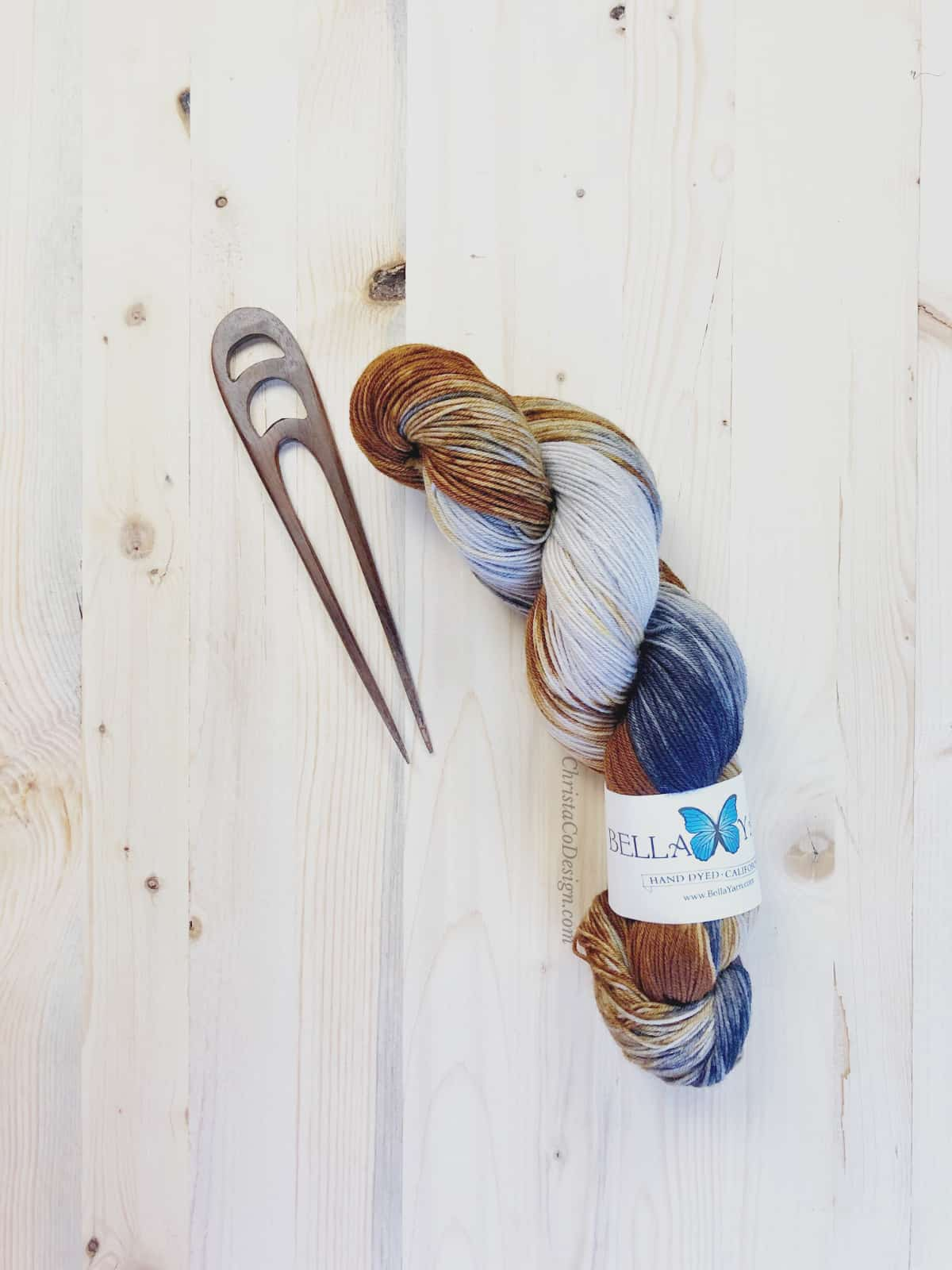 picture of grey, black and rust color hank of hand dyed yarn with wood shawl pin