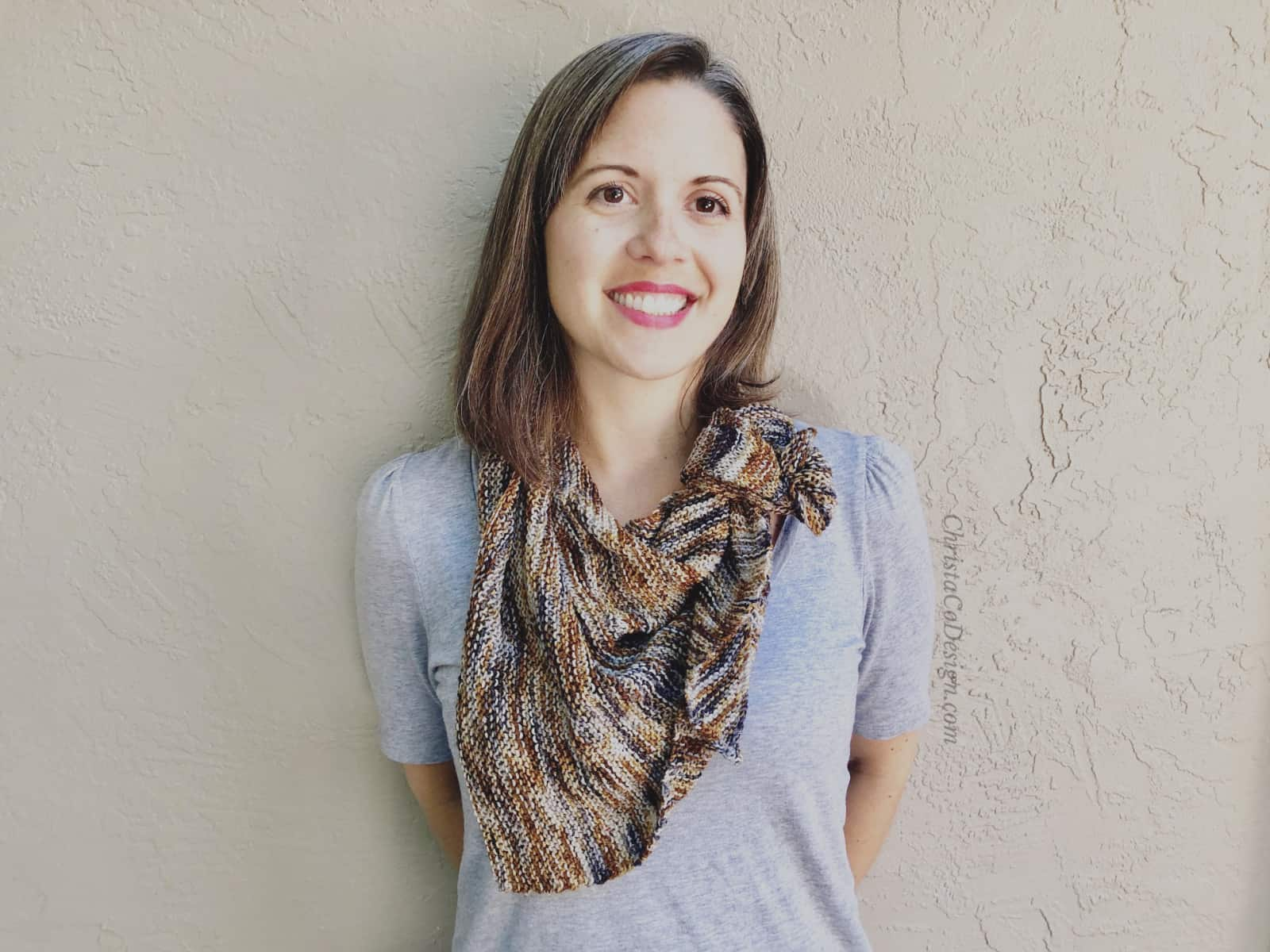 picture of dark haired woman in grey, black and rust color knit triangle scarf
