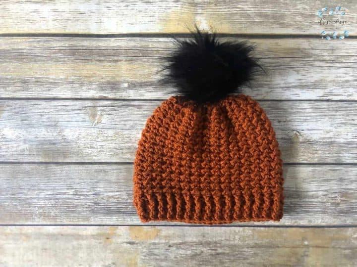 Texture crochet pattern in rust yarn with black pom pom bottom up.