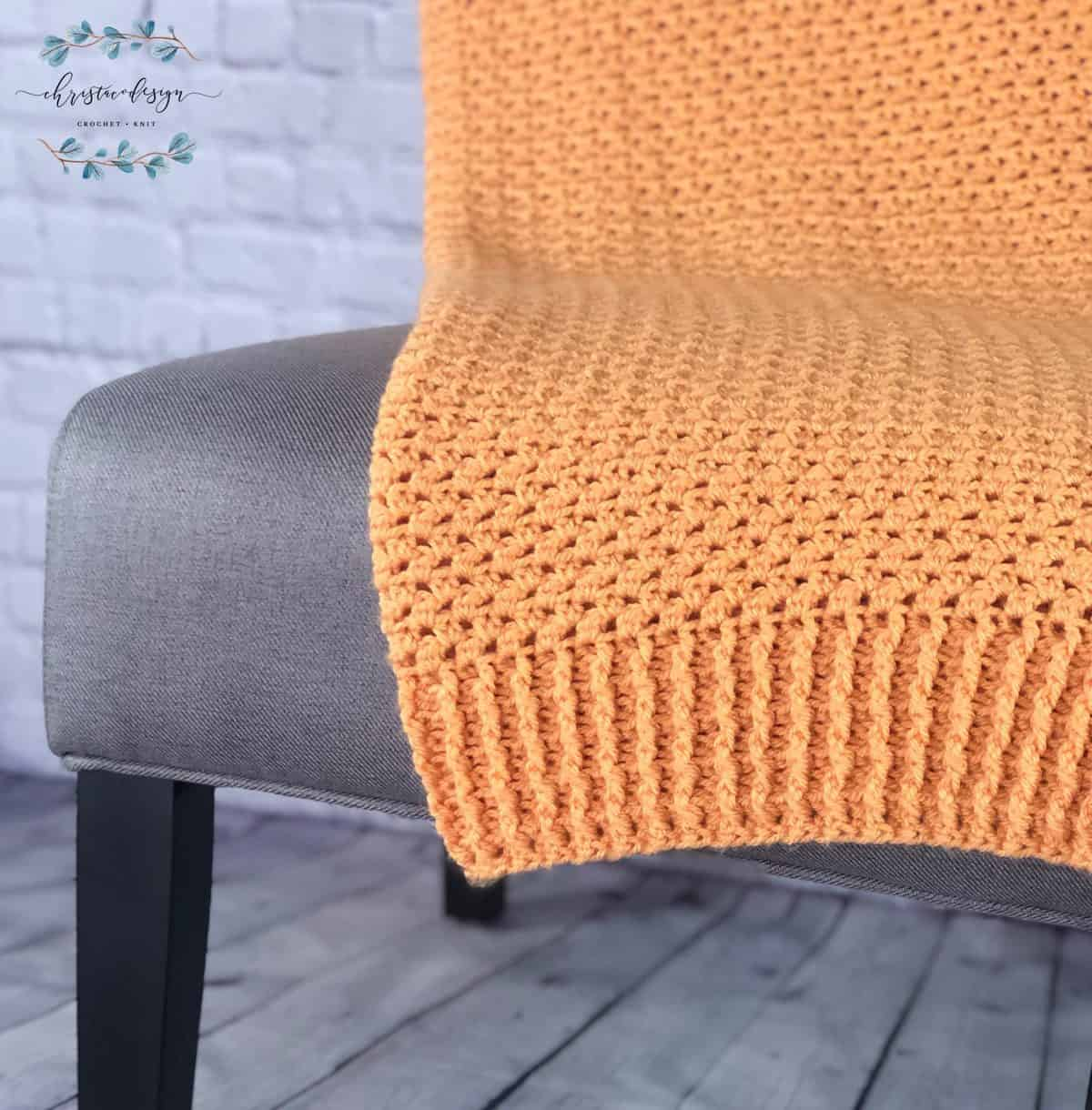 Orange crochet blanket with ribbed edging on grey chair.