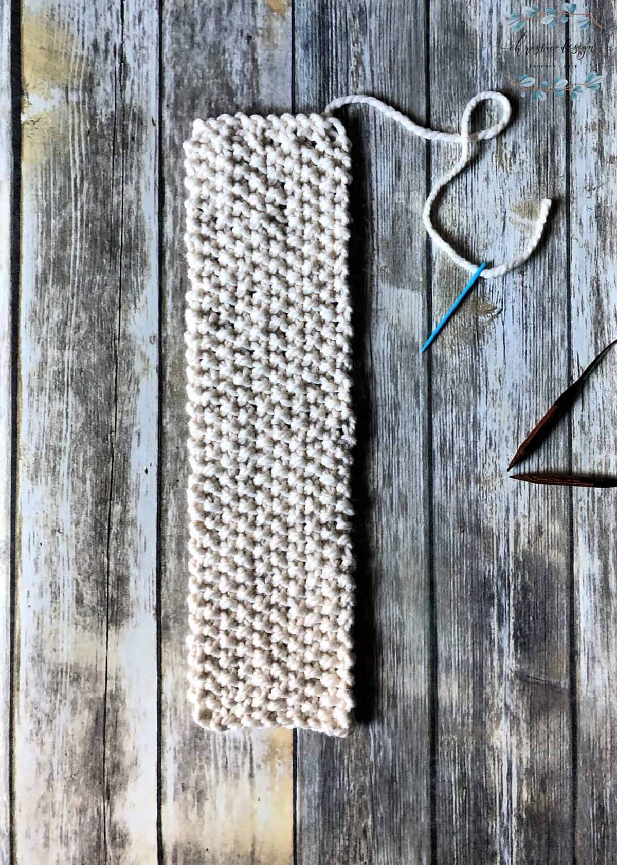 picture of knit ear warmer worked to length flat needle