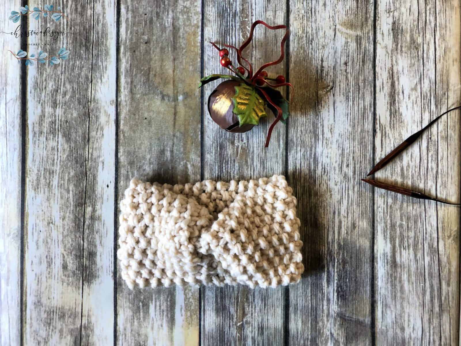 picture of chunky knit ear warmer in cream flat with Christmas bell and needles