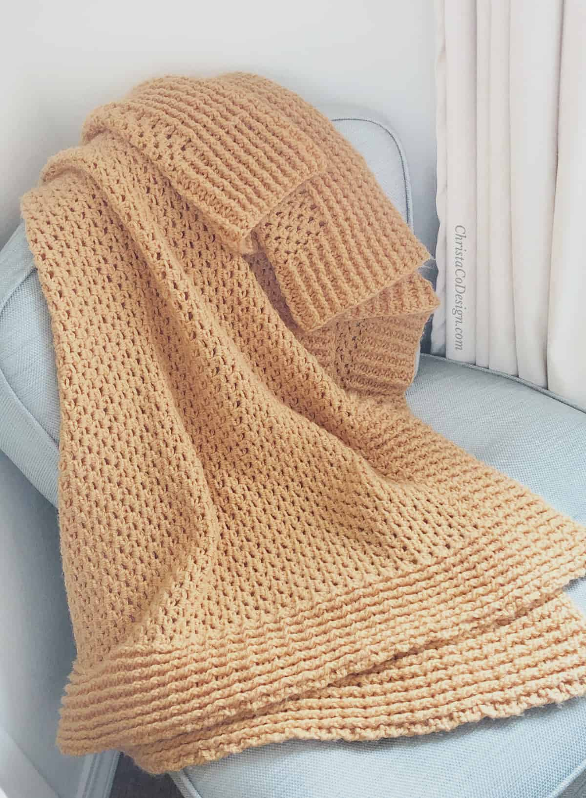 picture of crochet ribbed throw blanket in orange on blue chair