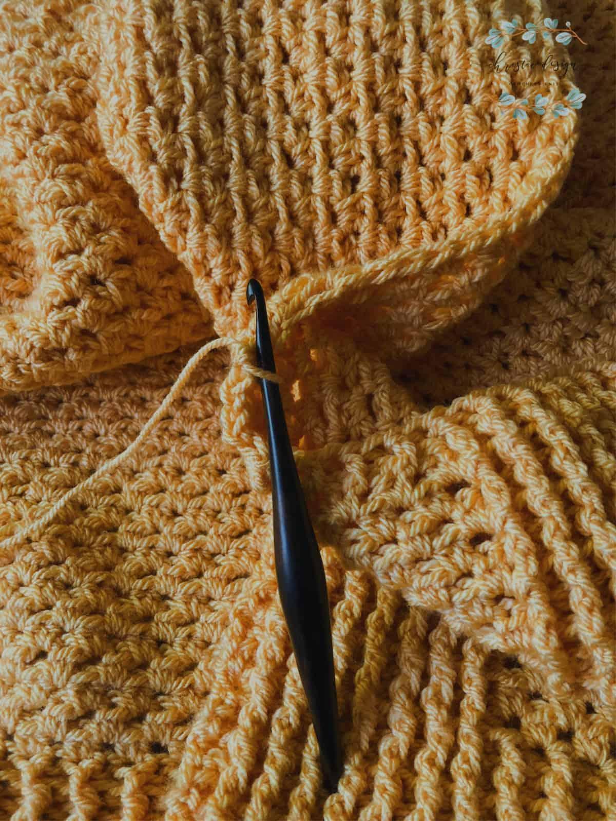 picture of orange blanket and wood crochet hook