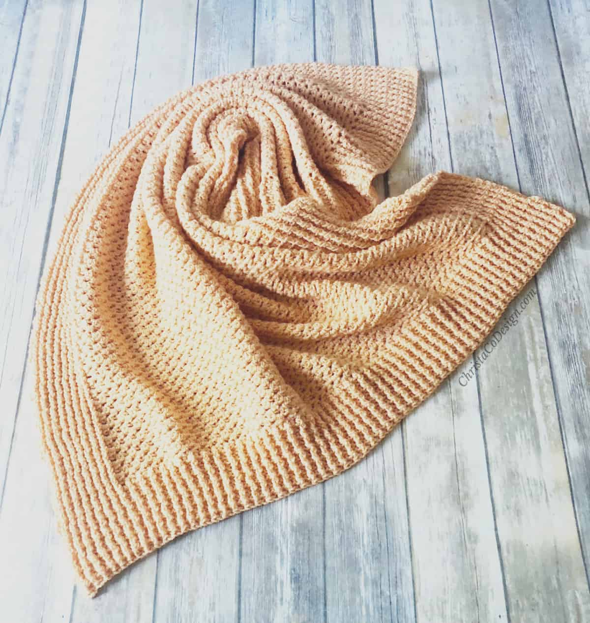 picture of orange crochet blanket twisted on wood floor