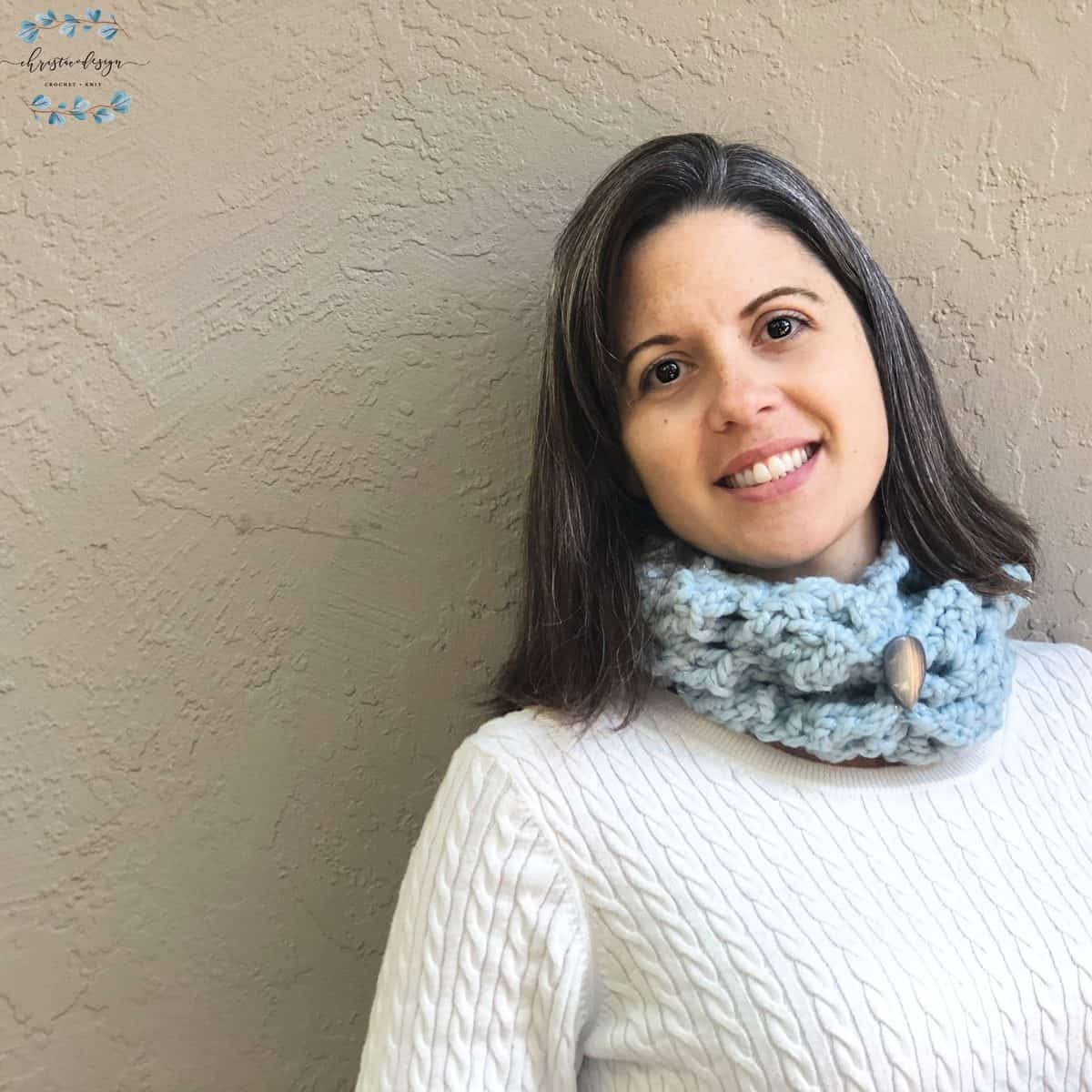 picture of woman smiling at camera with blue chunky cowl free pattern on neck