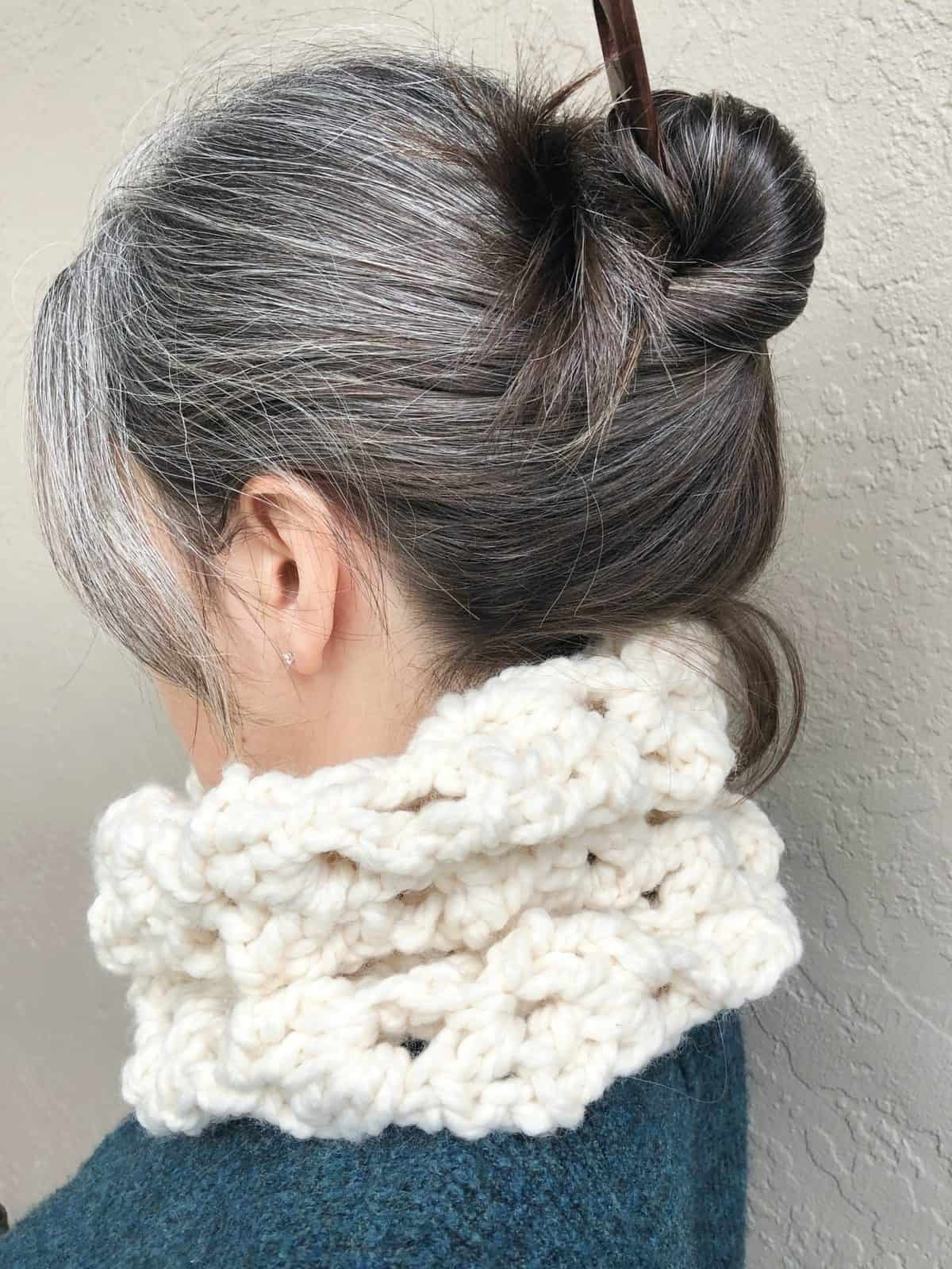 picture of woman turned away with chunky cream colored cowl around neck