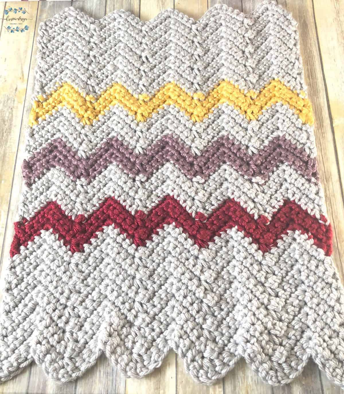 picture of jumbo yarn blanket in sliver, yellow, purple, red chevron stripes