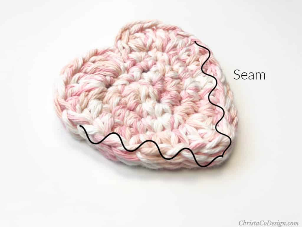 Crochet scrubby pattern in a pocket design of a heart pink and white variegated yarn.