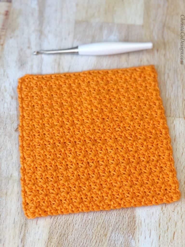 Trinity stitch crochet swatch in orange yarn with tutorial.