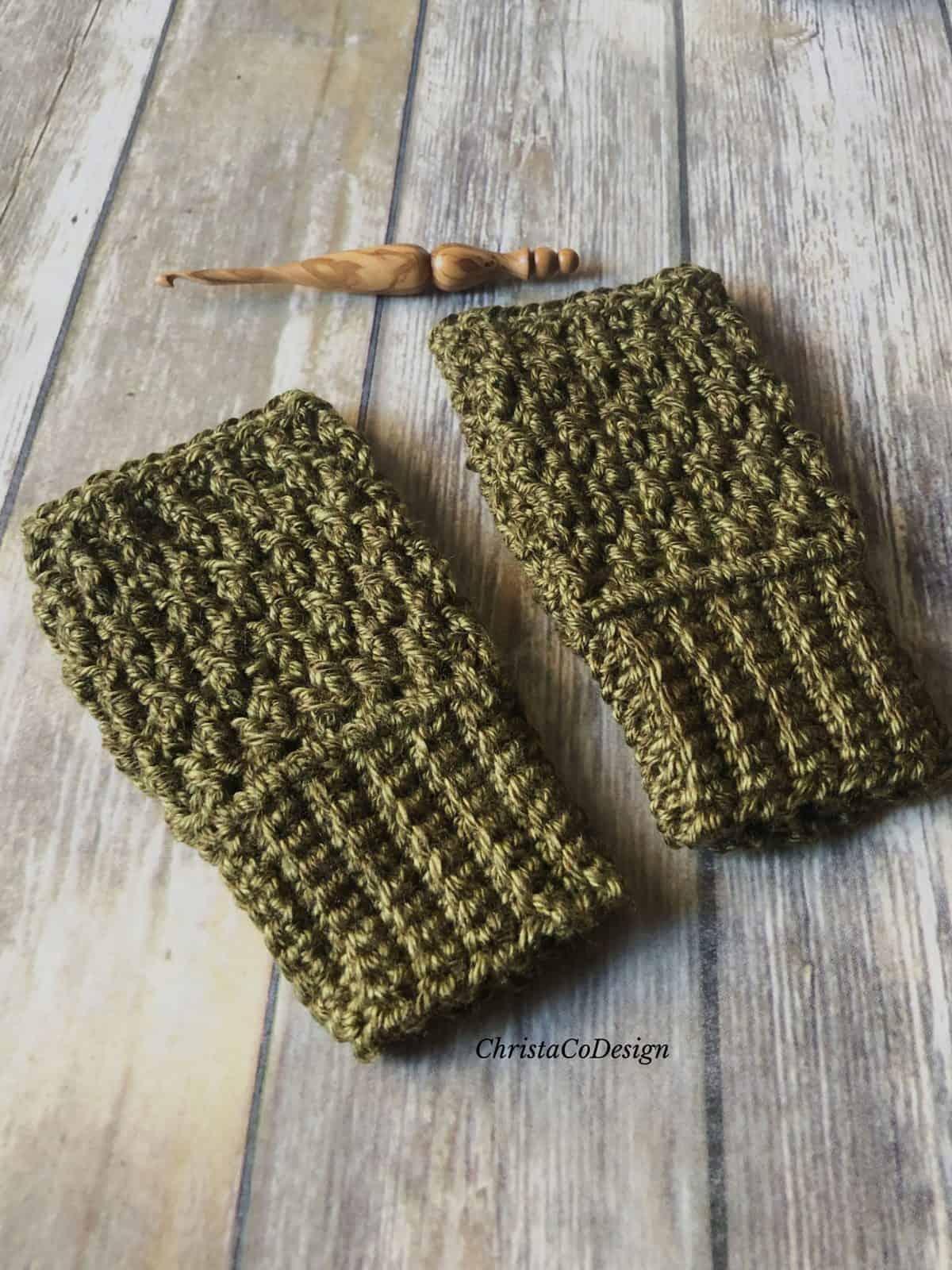 picture of dark green crochet fingerless gloves on wood floor with wood crochet hook