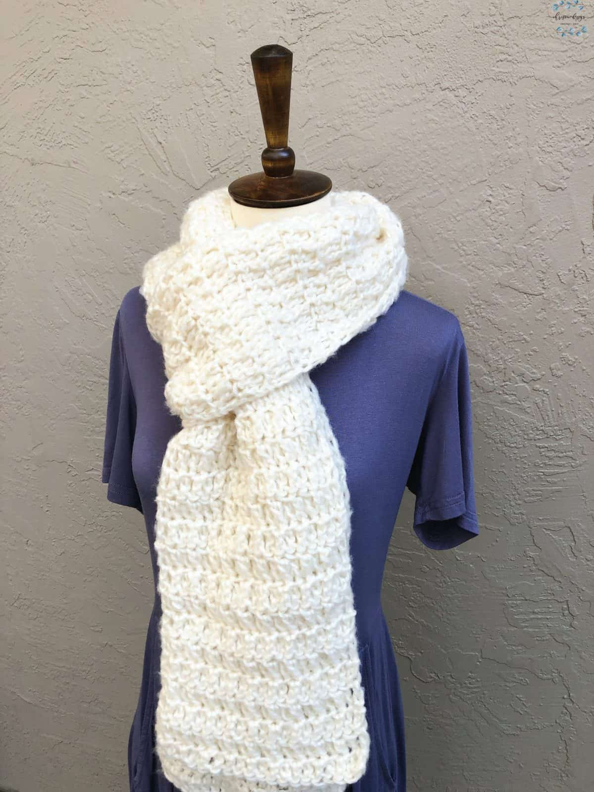 picture of long chunky white colored scarf on mannequin wearing purple dress