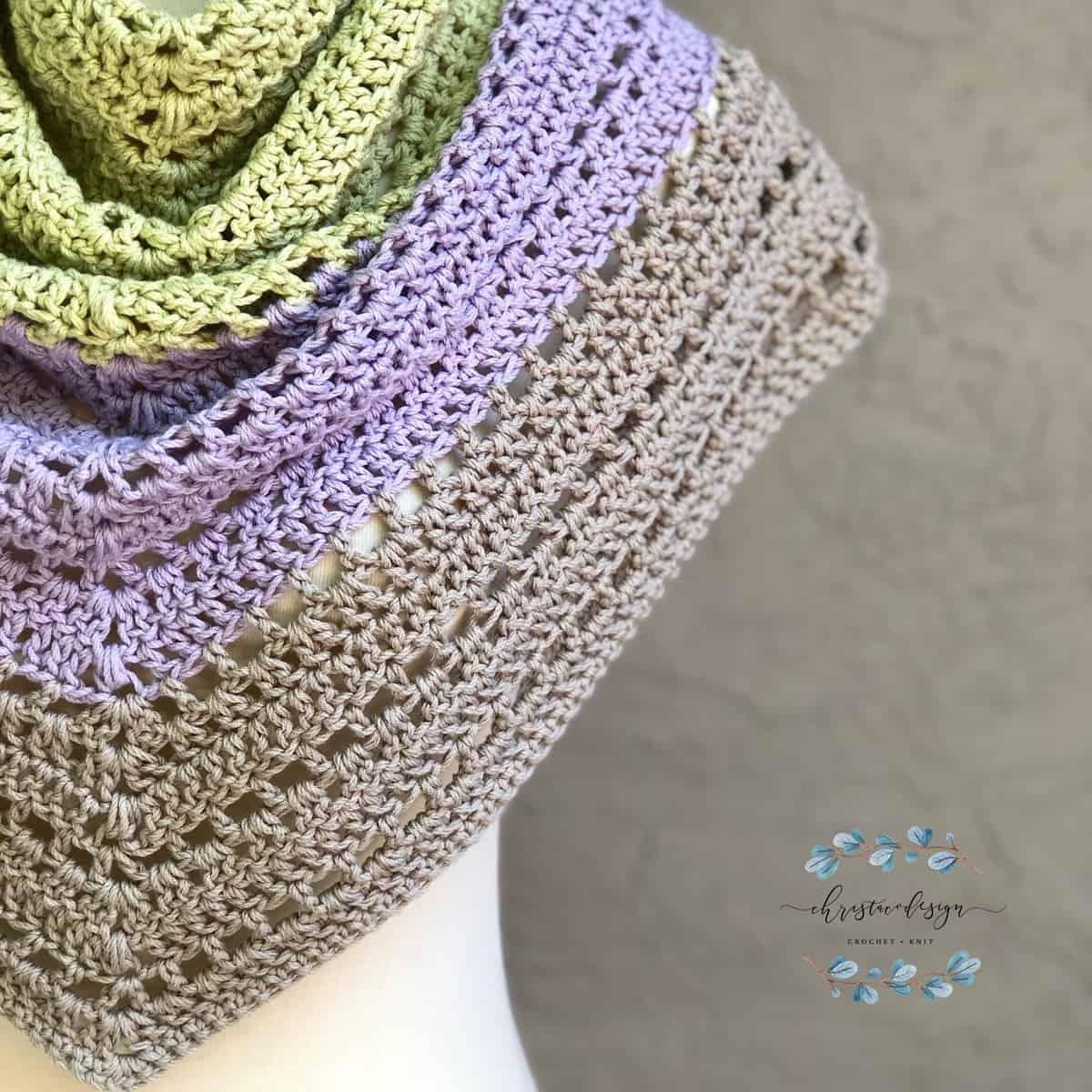 Lightweight summer crochet triangle shawl pattern in beige, purple and green.