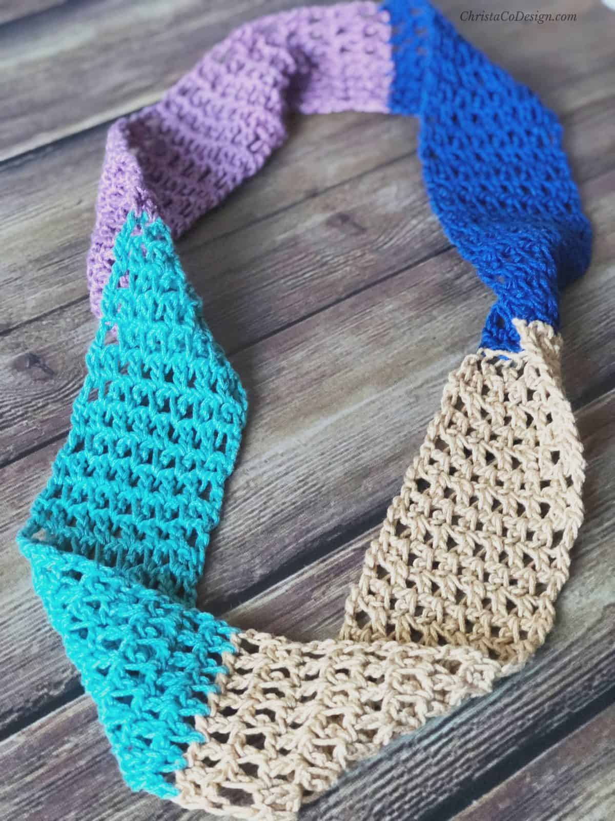 Laid flat: lacy crochet cowl with four colors.