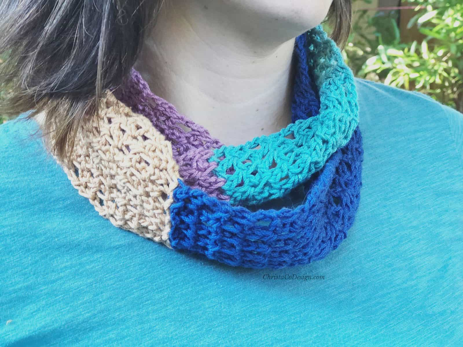Crochet cowl in multiple colors wrapped around woman's neck.
